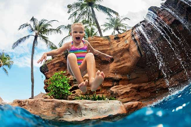 A girl jumping into a pool from a pool jumping rock.