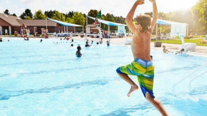 Boy jumping into public swimming pool